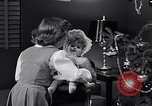 Image of decorated christmas tree and young girl with doll United States USA, 1951, second 8 stock footage video 65675032403