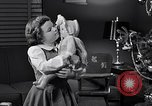 Image of decorated christmas tree and young girl with doll United States USA, 1951, second 12 stock footage video 65675032403