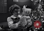 Image of decorated christmas tree and young girl with doll United States USA, 1951, second 14 stock footage video 65675032403
