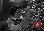 Image of decorated christmas tree and young girl with doll United States USA, 1951, second 15 stock footage video 65675032403