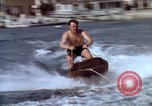 Image of motorboat pulling man and woman balanced on aquaplane United States USA, 1939, second 15 stock footage video 65675051556