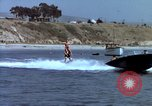Image of motorboat pulling man and woman balanced on aquaplane United States USA, 1939, second 25 stock footage video 65675051556