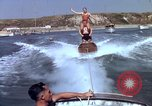 Image of motorboat pulling man and woman balanced on aquaplane United States USA, 1939, second 27 stock footage video 65675051556