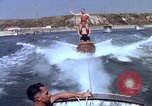 Image of motorboat pulling man and woman balanced on aquaplane United States USA, 1939, second 28 stock footage video 65675051556