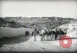 Image of Small boy walking with camels Amman Transjordan, 1945, second 7 stock footage video 65675062976