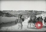 Image of Small boy walking with camels Amman Transjordan, 1945, second 15 stock footage video 65675062976